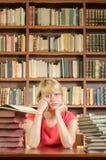 Étudiante inquiétée dans la bibliothèque avec des coudes sur la table Image stock