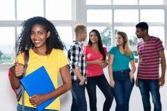 Étudiante latino-américaine avec le groupe d'autres jeunes adultes Image libre de droits