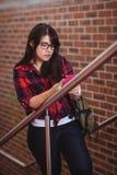 Étudiante marchant sur l'escalier tout en à l'aide du téléphone portable Photo libre de droits