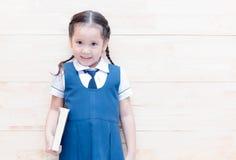 Étudiante mignonne heureuse dans l'uniforme avec le livre photos stock