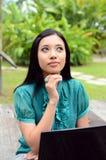 Étudiante musulmane assez asiatique de jeunes de portrait avec l'ordinateur portable et le sourire photos libres de droits