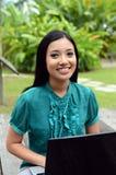 Étudiante musulmane assez asiatique de jeunes de portrait avec l'ordinateur portable et le sourire images libres de droits