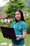Étudiante musulmane assez asiatique de jeunes de portrait avec l'ordinateur portable et le sourire image libre de droits