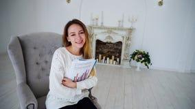 Étudiante Posing With Papers et dossiers, souriant, et se reposant dans la chaise Images stock