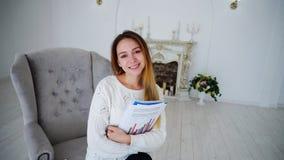 Étudiante Posing With Papers et dossiers, souriant, et se reposant dans la chaise Images libres de droits