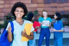 Étudiante réussie d'afro-américain avec le groupe d'étudiants photos libres de droits