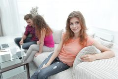 Étudiante s'asseyant avec des amis sur le divan Photographie stock libre de droits