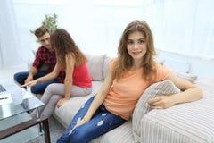 Étudiante s'asseyant avec des amis sur le divan Images libres de droits