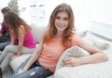 Étudiante s'asseyant avec des amis sur le divan Photo stock