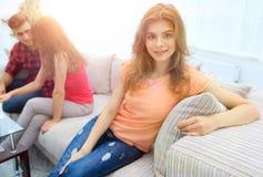 Étudiante s'asseyant avec des amis sur le divan Image stock