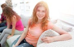 Étudiante s'asseyant avec des amis sur le divan Photographie stock