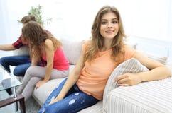 Étudiante s'asseyant avec des amis sur le divan Photos stock