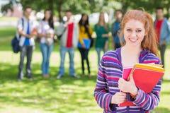 Étudiante tenant des livres avec des étudiants en parc Photographie stock