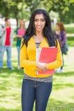 Étudiante tenant des livres avec les étudiants brouillés en parc Image libre de droits
