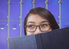 étudiante tenant le livre devant des casiers photographie stock