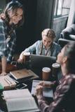Étudiantes buvant du café et étudiant ensemble au bureau Photos libres de droits