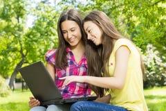 Étudiantes de sourire à l'aide de l'ordinateur portable Images libres de droits