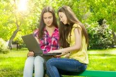 Étudiantes de sourire à l'aide de l'ordinateur portable Photographie stock libre de droits