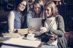 Étudiantes en café utilisant le comprimé numérique et l'animal familier de avoir Images libres de droits