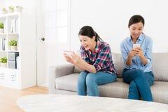 Étudiantes heureuses de beauté s'asseyant sur le sofa Photos libres de droits