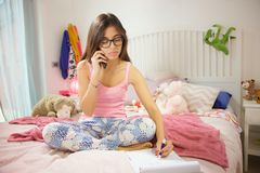 Étudiantes s'asseyant dans la chambre à coucher faisant le travail parlant au téléphone Images stock