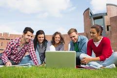 Étudiants à l'aide de l'ordinateur portable dans la pelouse contre le bâtiment d'université Photo libre de droits
