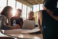 Étudiants à l'aide de l'ordinateur portable tout en se reposant ensemble dans la classe Photo stock