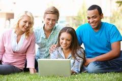Étudiants à l'aide de l'ordinateur portatif à l'extérieur Images stock