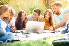 Étudiants à l'aide de l'ordinateur portatif à l'extérieur Photo stock