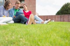 Étudiants à l'aide de la tablette dans la pelouse contre le bâtiment d'université Photos libres de droits