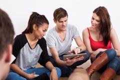 Étudiants à l'aide de la Tablette de Digital sur le plancher photographie stock