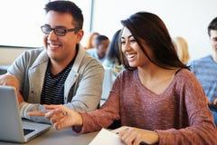 Étudiants à l'aide de la Tablette et de l'ordinateur portable de Digital dans la classe Image stock