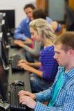 Étudiants à l'aide des ordinateurs dans la salle des ordinateurs Photo stock