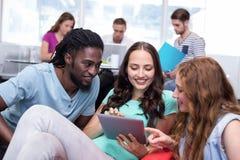 Étudiants à l'aide du comprimé numérique avec des amis à l'arrière-plan Photo libre de droits