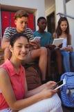Étudiants à l'aide du téléphone portable et du comprimé numérique sur l'escalier Photographie stock