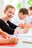 Étudiants écrivant un essai dans la concentration d'école Image libre de droits