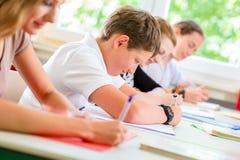 Étudiants écrivant un essai dans la concentration d'école Images libres de droits