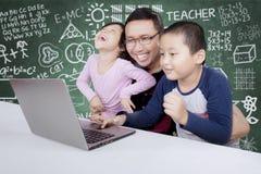 Étudiants élémentaires à l'aide d'un ordinateur portable avec leur professeur Images stock