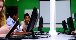 Étudiants étudiant sur l'ordinateur dans la salle de classe banque de vidéos