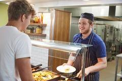 Étudiants adolescents étant servis le repas dans la cantine scolaire image stock