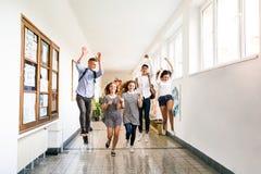 Étudiants adolescents dans le hall de lycée sautant haut Photos libres de droits