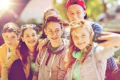 Étudiants adolescents heureux prenant le selfie par le smartphone Photos stock