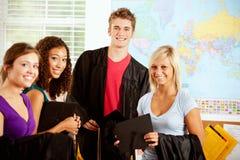 Étudiants : Ados dans la classe avec des chapeaux et des robes d'obtention du diplôme photographie stock