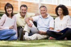 Étudiants adultes s'asseyant sur une pelouse de campus Image libre de droits