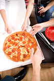 Étudiants : Amis atteignant dedans pour saisir la tranche de pizza Photo stock