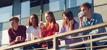 Étudiants appréciant la tasse de café pour aller sur la rue Image stock