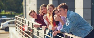Étudiants appréciant la tasse de café pour aller sur la rue Photo stock