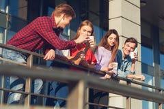 Étudiants appréciant la tasse de café pour aller sur la rue Photographie stock libre de droits