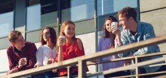 Étudiants appréciant la tasse de café pour aller sur la rue Photo libre de droits