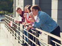 Étudiants appréciant la tasse de café pour aller sur la rue Photographie stock